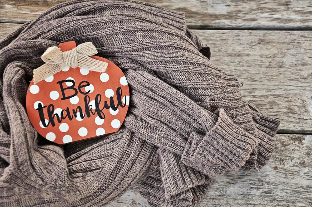 be thankful ornament on sweater with wood backdrop
