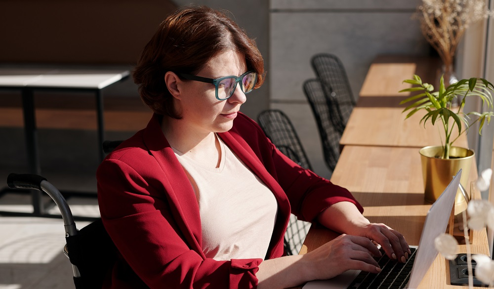 woman in wheelchair and red jacket at laptop typing