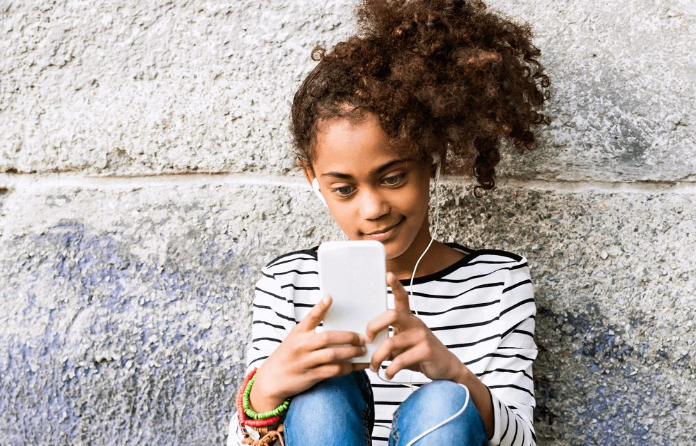 young girl in striped shirt with ponytail and headphones reading phone
